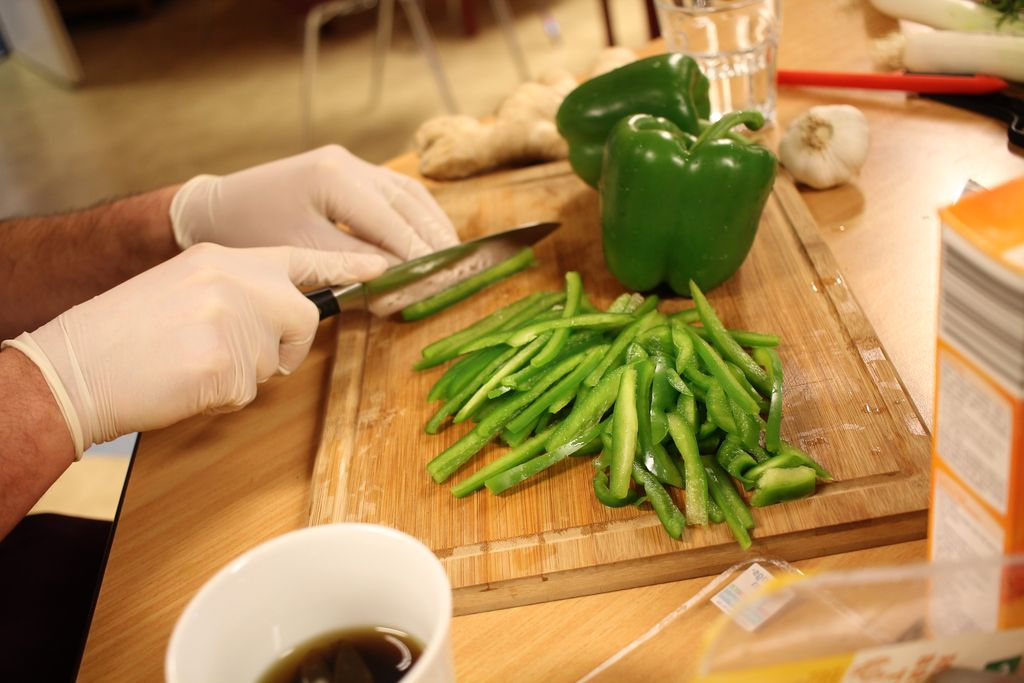 Vorbereitung ist alles - Fleißige Hände schneiden Paprika in feine Streifen.