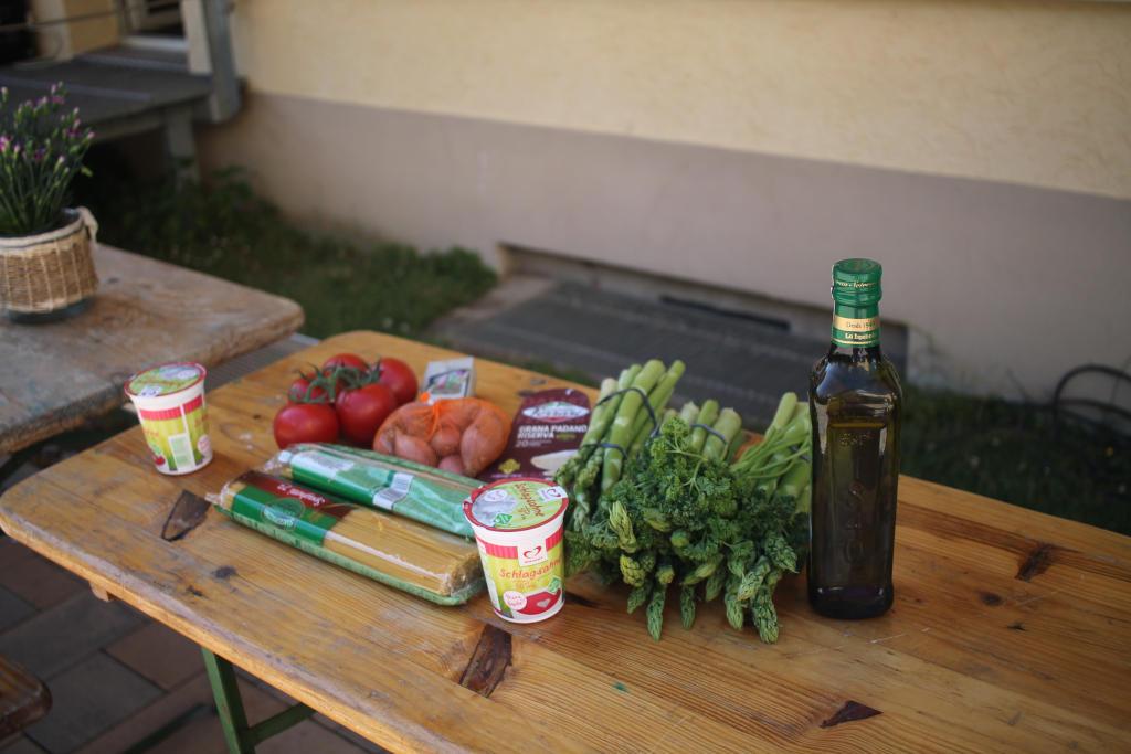 Auf einem Tisch liegen die Zutaten für Spaghetti mit gebratenem grünen Spargel