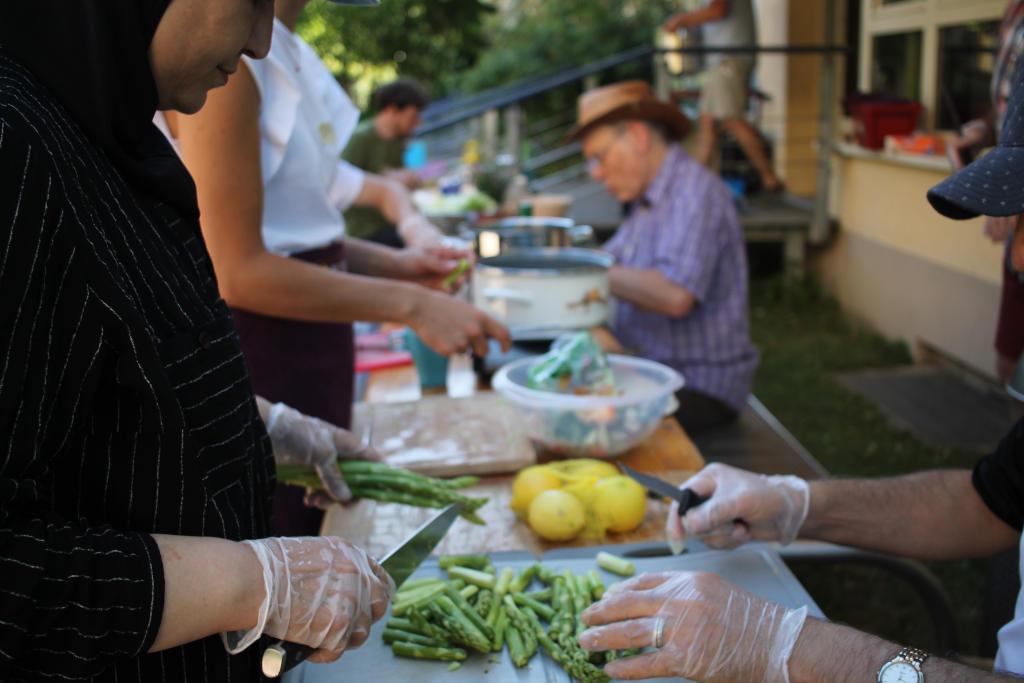 Viele Hände helfen bei der Zubereitung von Spaghetti mit gebratenem grünen Spargel